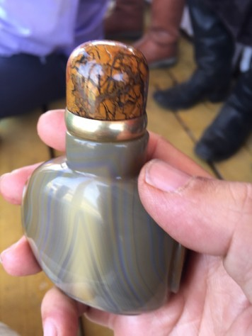 The snuff bottle is intricately made from precious stones.