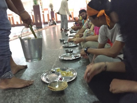 As we put our trays on the marble floor, volunteers scoop different curry onto the trays down the row.