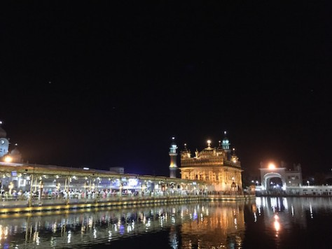 The Golden Temple glitters brightly over the pool at night.