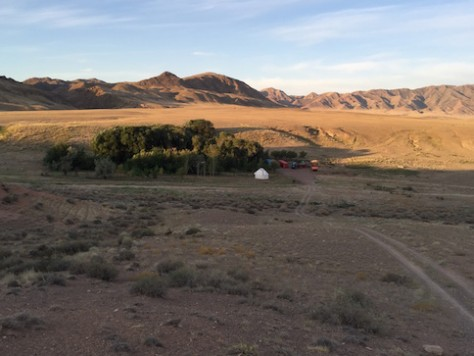 The campsite is located in a desert valley next to a natural water spring.