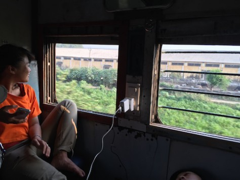Using and charging our devices on the train in India.
