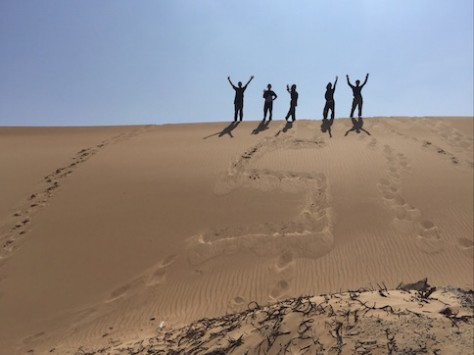 "To celebrate traveling for 5 months, we etched ""5"" on the sand dune of Oman."