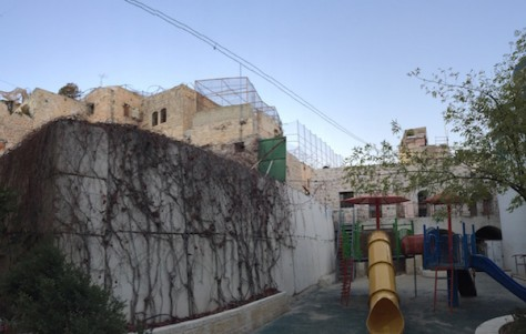 The playground in the Jewish settlement is surrounded military barracks on the rooftop constantly guarding the settler children. The walls of the arab houses are right next to the Jewish walls.