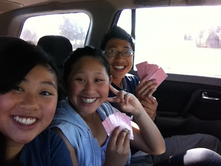 The children played card games in the back of the car during breaks between homework.
